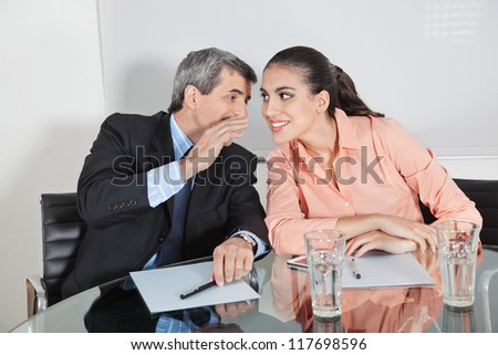 Manager whispering a secret into the ear of a businesswoman - stock photo