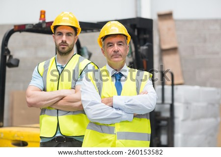 Manager with arms crossed and his colleague behind him - stock photo