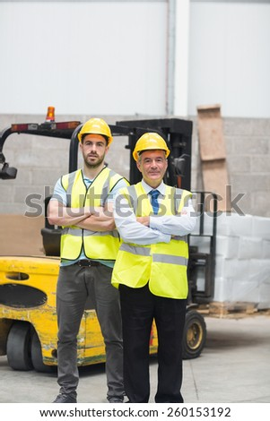 Manager with arms crossed and his colleague behind him in warehouse - stock photo