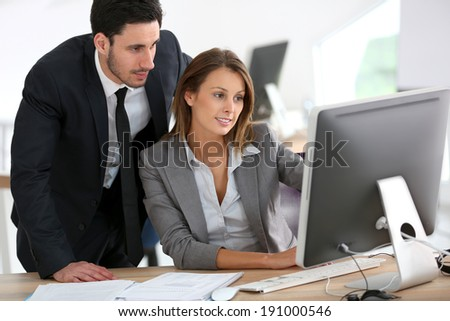 Manager with businesswoman working on desktop - stock photo