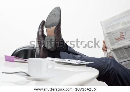 manager with feet on desk and cup of coffee - stock photo