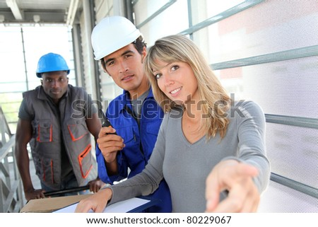 Manager with store men controlling goods delivery - stock photo