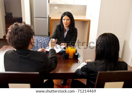 Manager woman giving  to a business man a contract for signing at job interview - stock photo