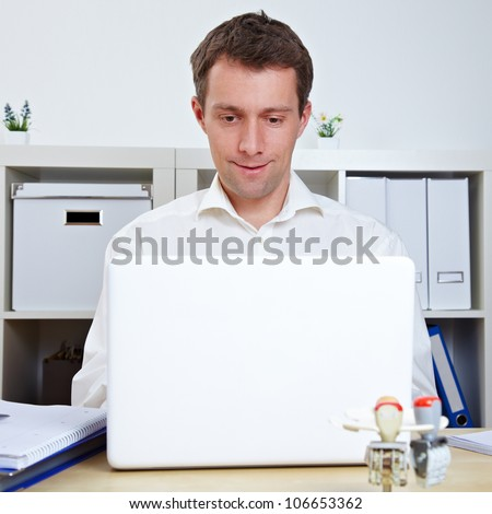 Manager working at his desk with laptop in the office - stock photo