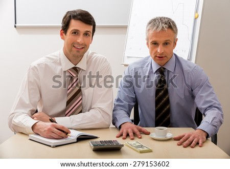 Managers calculate the profit. Two bosses make a business plan. - stock photo