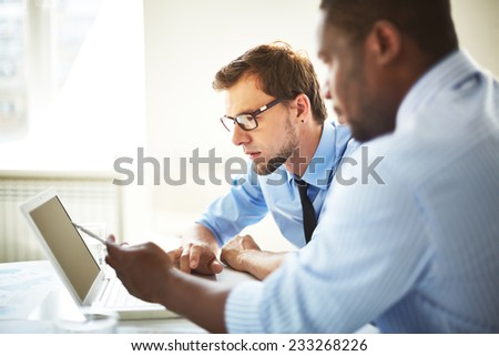 Managers discussing something on laptop - stock photo