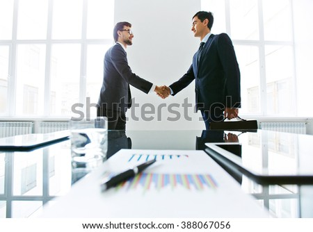 Managers meeting and shaking hands in board room - stock photo