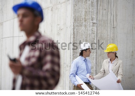 Managers with blueprint and blurred worker in foreground at construction site