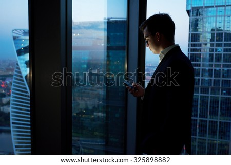 Managing director dressed in elegant clothes using mobile phone while resting after late briefing in the nighttime, young smart male entrepreneur read text message on cell telephone during work break - stock photo