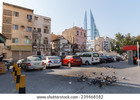 Manama, Bahrain - November 21, 2014: Street view with an old living houses and Bahrain World Trade Center in Manama city, Capital of Bahrain. Middle East - stock photo