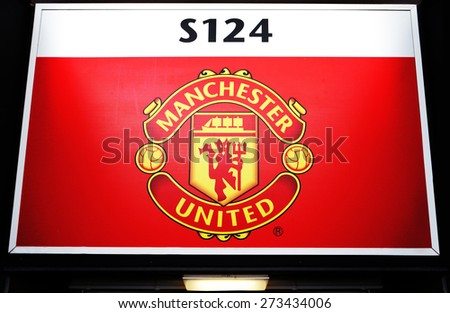 MANCHESTER, ENGLAND - FEBRUARY 17: Logo on a cutout over an entrance gate of the Old Trafford stadium on February 17 ,2014 in Manchester, England. Old Trafford is home to Manchester United. - stock photo