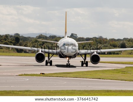 Manchester, United Kingdom - August 27, 2015: Monarch Airways Airbus A320 passenger plane taxiing on Manchester International Airport taxiway after landing.