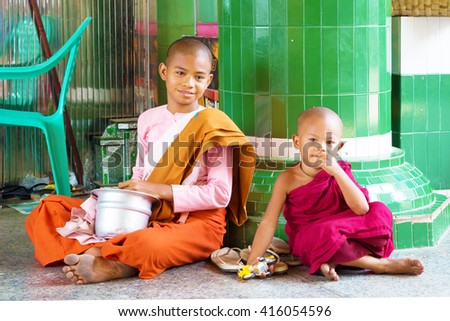 Mandalay, Myanmar - April 21, 2016:. Elder girl and child dressed as buddhist nun and monk. They are sitting close to the column of a temple. - stock photo