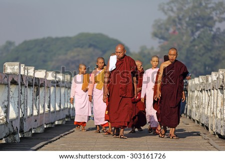 MANDALAY, MYANMAR- DEC 9 : Unidentified monks and nun walk at U Bein Bridge on Dec 9, 2014 in Mandalay. The Most popular travel destinations and longest wood bridge in the world. - stock photo