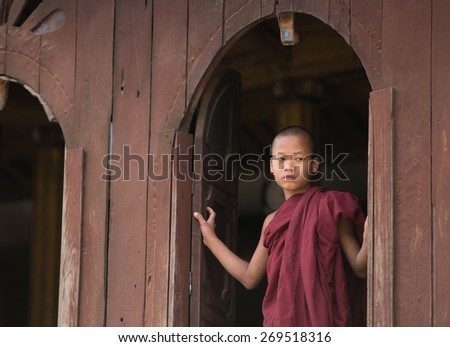 MANDALAY, MYANMAR - DECEMBER 8, 2014. An unidentified Burmese Buddhist novice in Mandalay, Myanmar. In 2012 an ongoing conflict started between Buddhists and Muslims in Myanmar. - stock photo