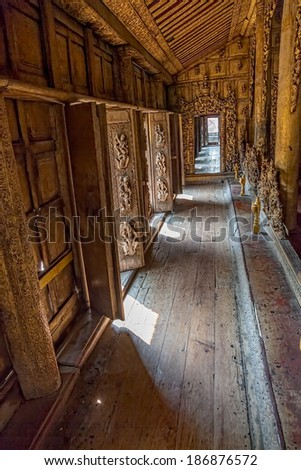 MANDALAY, MYANMAR - FEBRUARY 26, 2013: Shwenandaw Kyaung Temple or Golden Palace Monastery hallway. This is the only building that remains of the old Mandalay Palace which burnt down during WWII. - stock photo