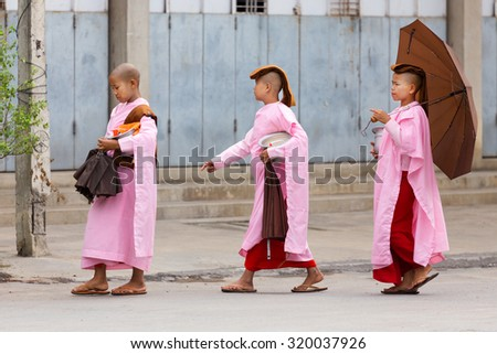 MANDALAY,MYANMAR,JANUARY 17, 2015: A group of young Buddhist nuns is walking in the streets of Mandalay, Myanmar (Burma). - stock photo