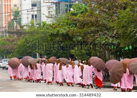 MANDALAY,MYANMAR,JANUARY 17, 2015 : A row of young Buddhist nuns is walking in the streets of Mandalay, Myanmar (Burma). - stock photo