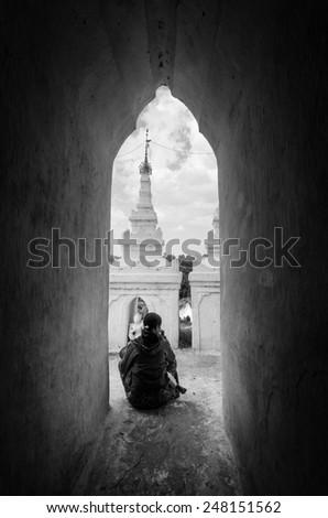 Mandalay, Myanmar - January 16, 2015 .Silhouette figure of women sitting on the arch corridor of Hsinbyume Myatheindan Pagoda White Temple in Mingun, near Mandalay in Myanmar (Burma) Black and white. - stock photo
