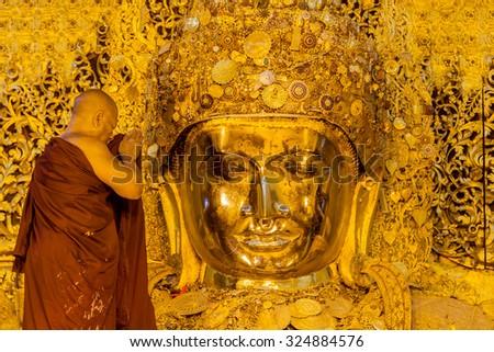 Mandalay, Myanmar-January 25: The senior monk wash Mahamuni Buddha image in ritual of the Buddha image face wash every morning at 4am. on January 25,2013 at Mahamuni temple in Mandalay, Myanmar. - stock photo