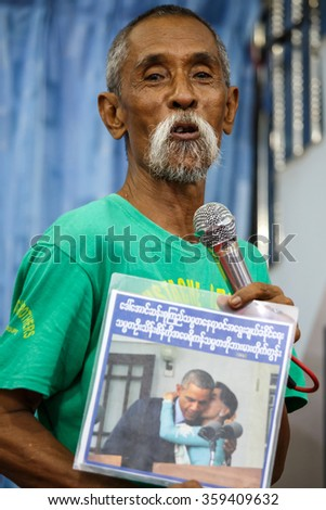 MANDALAY, MYANMAR - JUNE 25 2015: Moutache brother shows photo of President Obamma kissing Aung San Suu Kyi in Mandalay, Myanmar. - stock photo