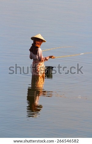 MANDALAY, MYANMAR - NOVEMBER 8: A local Burmese lady in traditional dress fishing in Taungthaman Lake near the U Bein Bridge, Mandalay, Myanmar on the 8th November 2012. - stock photo