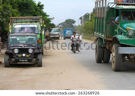 MANDALAY, MYANMAR - NOVEMBER 7: A street scape view of the dusty road with traffic in the town of Mandalay, Myanmar on the 7th November 2012.