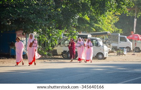 MANDALAY, MYANMAR- NOVEMBER 25 :The buddhist nuns are walking along a street in city on November 25, 2015 in Mandalay,Myanmar  - stock photo