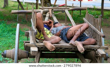 MANDALAY, MYANMAR - NOVEMBER 14: Two young Burmese men asleep in the back of an ox cart under the shade of a tree in Bagan near Mandalay, Myanmar on the 14th November, 2012. - stock photo
