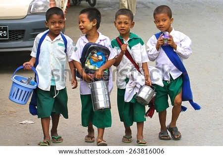 MANDALAY, MYANMAR - NOVEMBER 7: Young Burmese boys with tiffin boxes and thanaka on their faces in school uniform walking along the road in the town of Mandalay, Myanmar on the 7th November, 2012. - stock photo