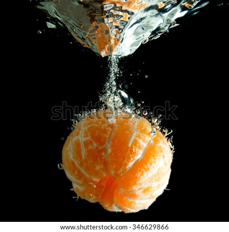 Mandarin falls into the water isolated on a black background - stock photo