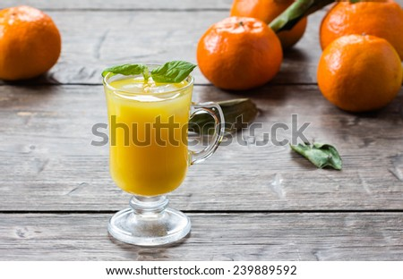 Mandarin  juice with leaf mint and ice cube on wooden background  - stock photo