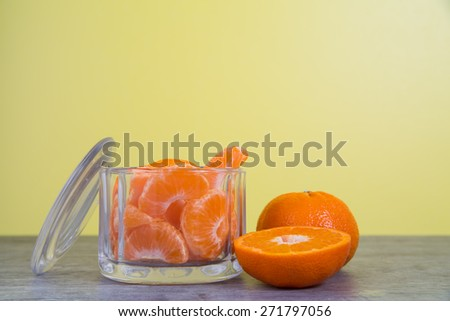 Mandarin orange slices in a glass jar sit on a wooden table with a bright yellow background - stock photo