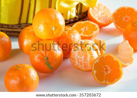 Mandarin peeled ripe sliced wicker basket , white background spilled