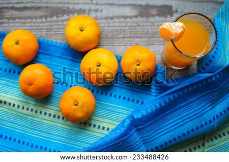 Mandarine fresh fruits and juice on the old table - stock photo