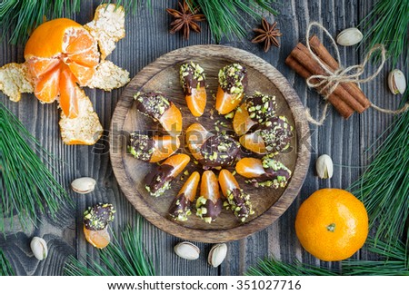 Mandarins covered with chocolate and pistachio, top view - stock photo