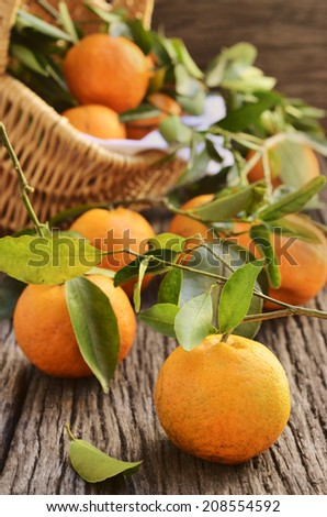 mandarins with a green leaves in a basket and on a wooden rustic background