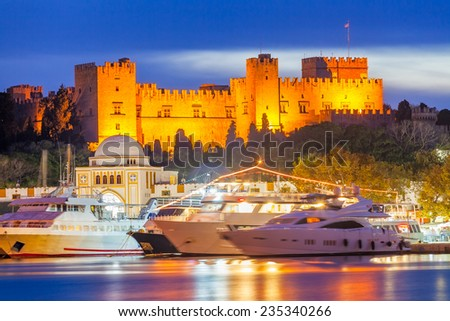 Mandraki Harbour Rhodes Greece and The Palace of the Grand Master of the Knights of Rhodes at night. - stock photo