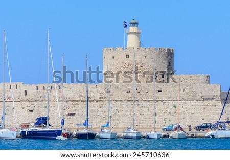 MANDRAKI PORT, RHODES ISLAND - JUNE 28, 2014: Old fortress with lighthouse in the port of Mandraki on June 28 2014.. Greek islands are popular tourist destination for many Europeans.
