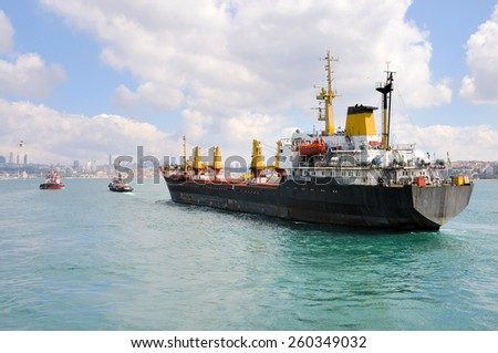 Maneuvers at sea on a cloudy day - Escorting ship by tugs. - stock photo