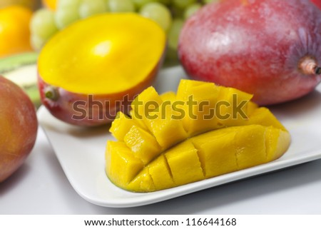 Mango and fruits on the plate closeup