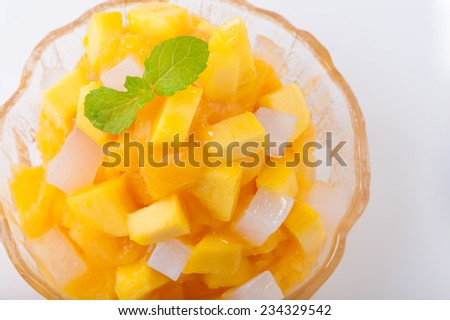 Mango flavoured shave ice with pieces of mango and coconut jelly. - stock photo