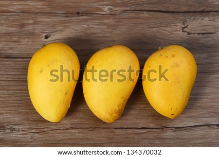 Mango fruit on a wooden background - stock photo