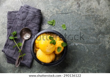 Mango ice cream sorbet with mint leaves on stone slate background - stock photo