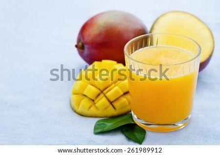 mango juice and fresh mango on a blue background. tinting. selective focus - stock photo