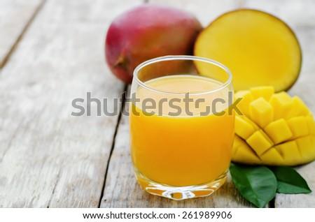 mango juice and fresh mango on a white wood background. tinting. selective focus - stock photo