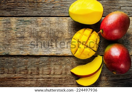 mango on a dark wood background. tinting. selective focus on the mangos slices - stock photo