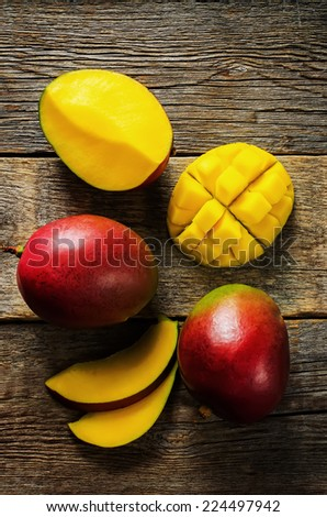 mango on a dark wood background. tinting. selective focus on the mangos slices - stock photo