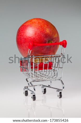 Mango placed in a small shopping cart on a grey reflective background. - stock photo