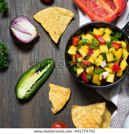Mango salsa in the bowl and ingredients on the wooden rustic table. Super foods. Mexican cuisine. Vegetarian concept.